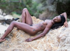 Naked black model posing on the river